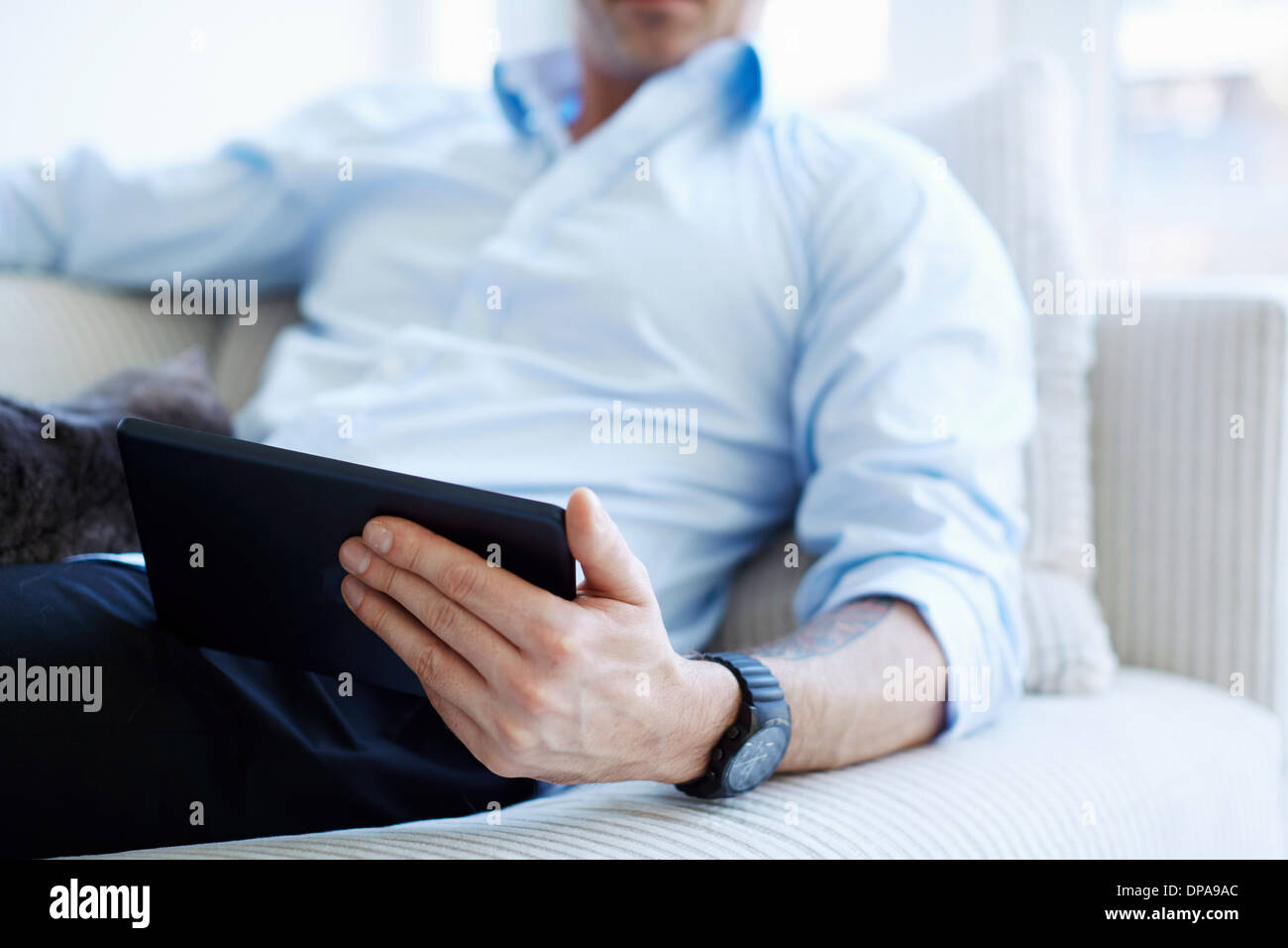 Cropped shot of man's midsection holding digital tablet - Stock Image