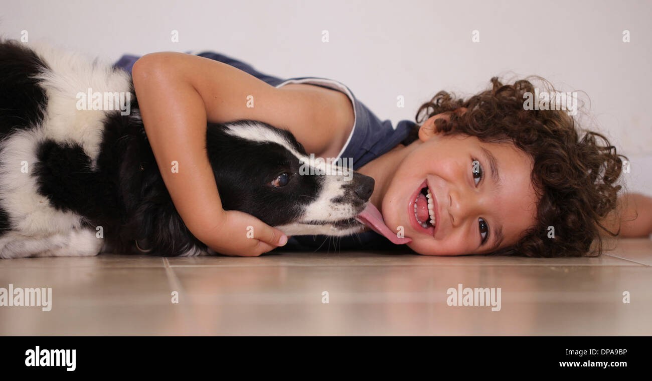 Young boy lying on floor hugging his pet dog - Stock Image