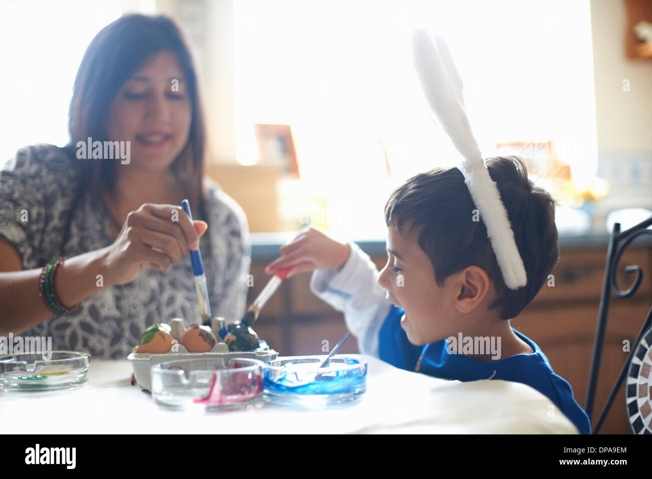 Woman and boy wearing bunny ears painting Easter eggs - Stock Image