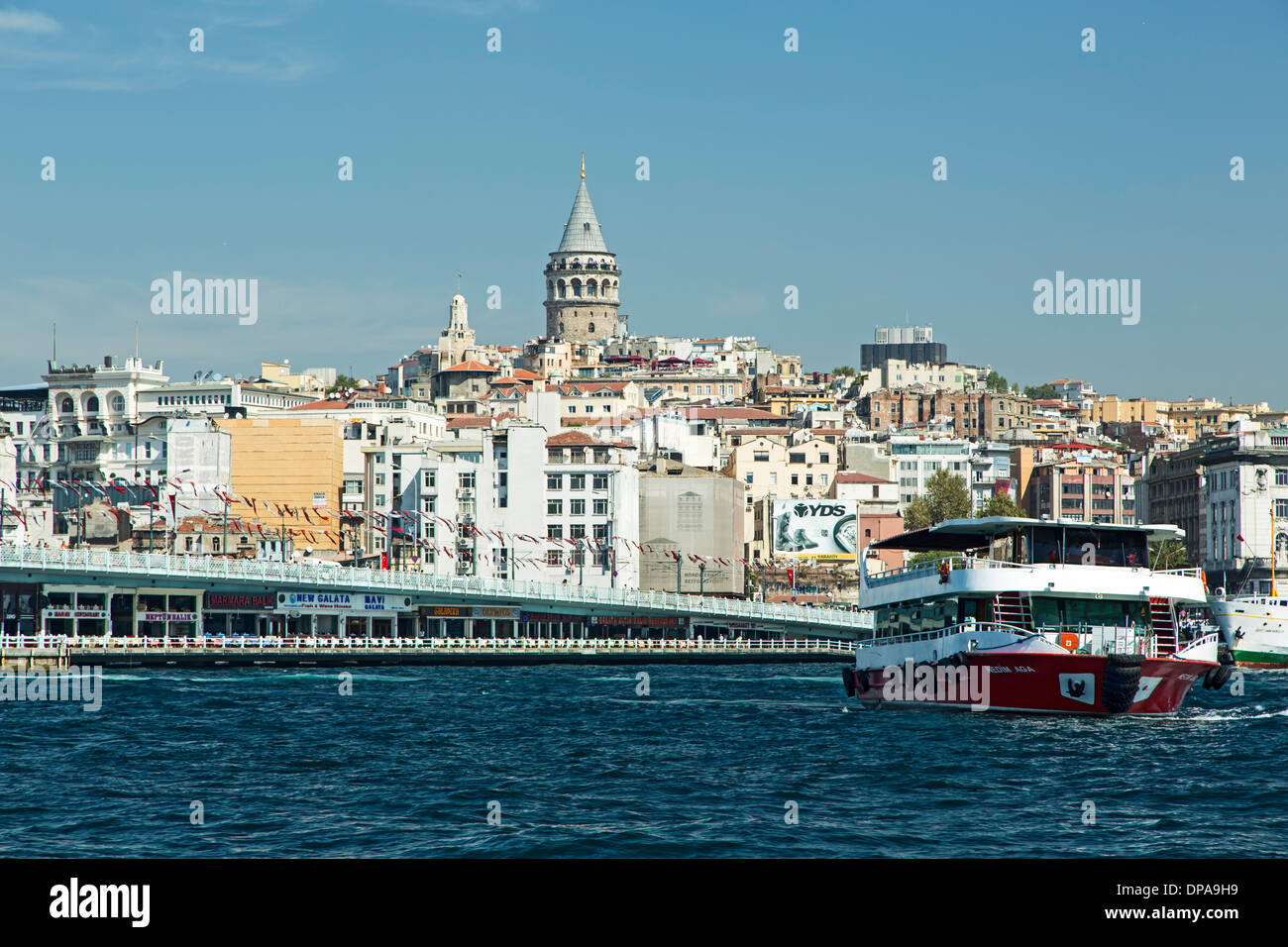 Ship on Golden Horn near Galata Bridge, Galata Tower in background, Istanbul, Turkey - Stock Image