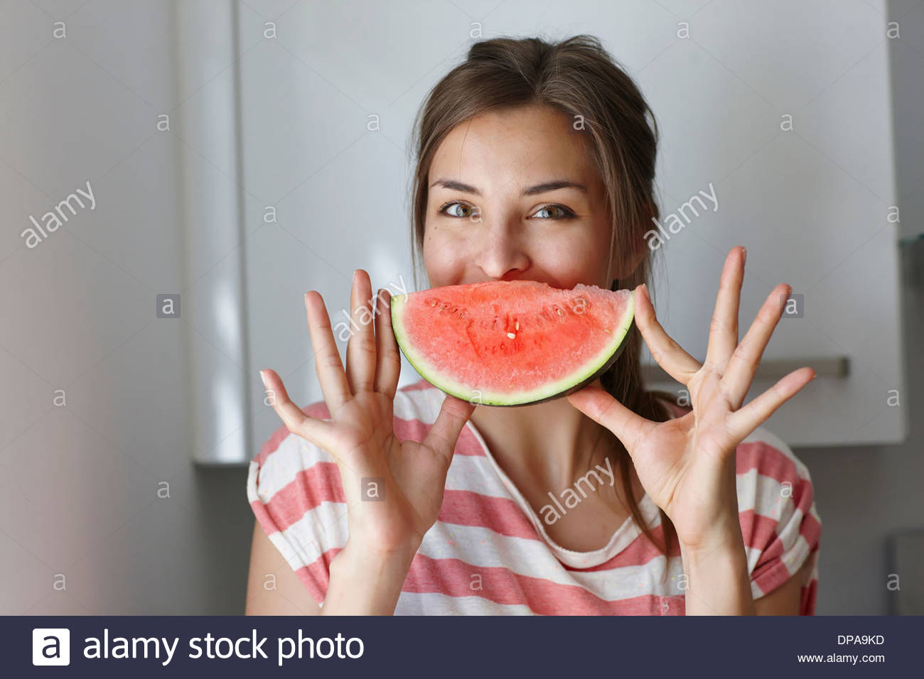 Woman covering mouth with slice of watermelon - Stock Image