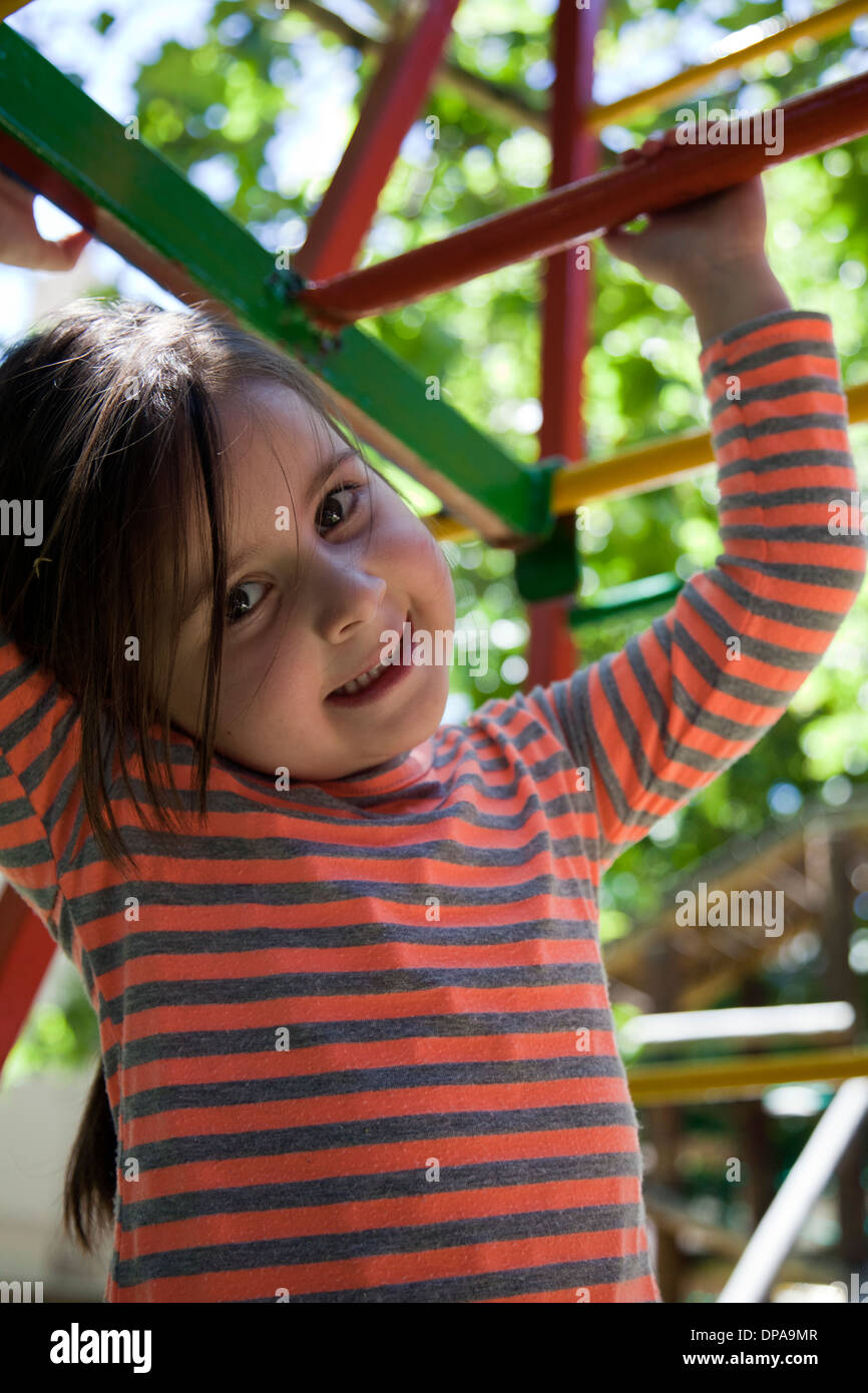 Girl on Playground Monkey Bars - Stock Image