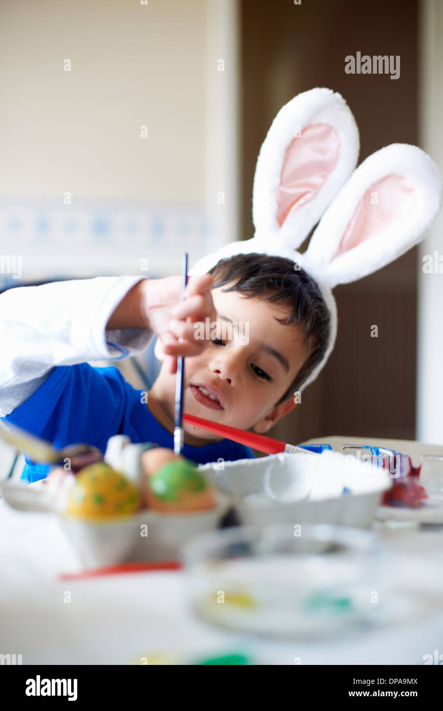 Boy wearing bunny ears painting Easter eggs - Stock Image