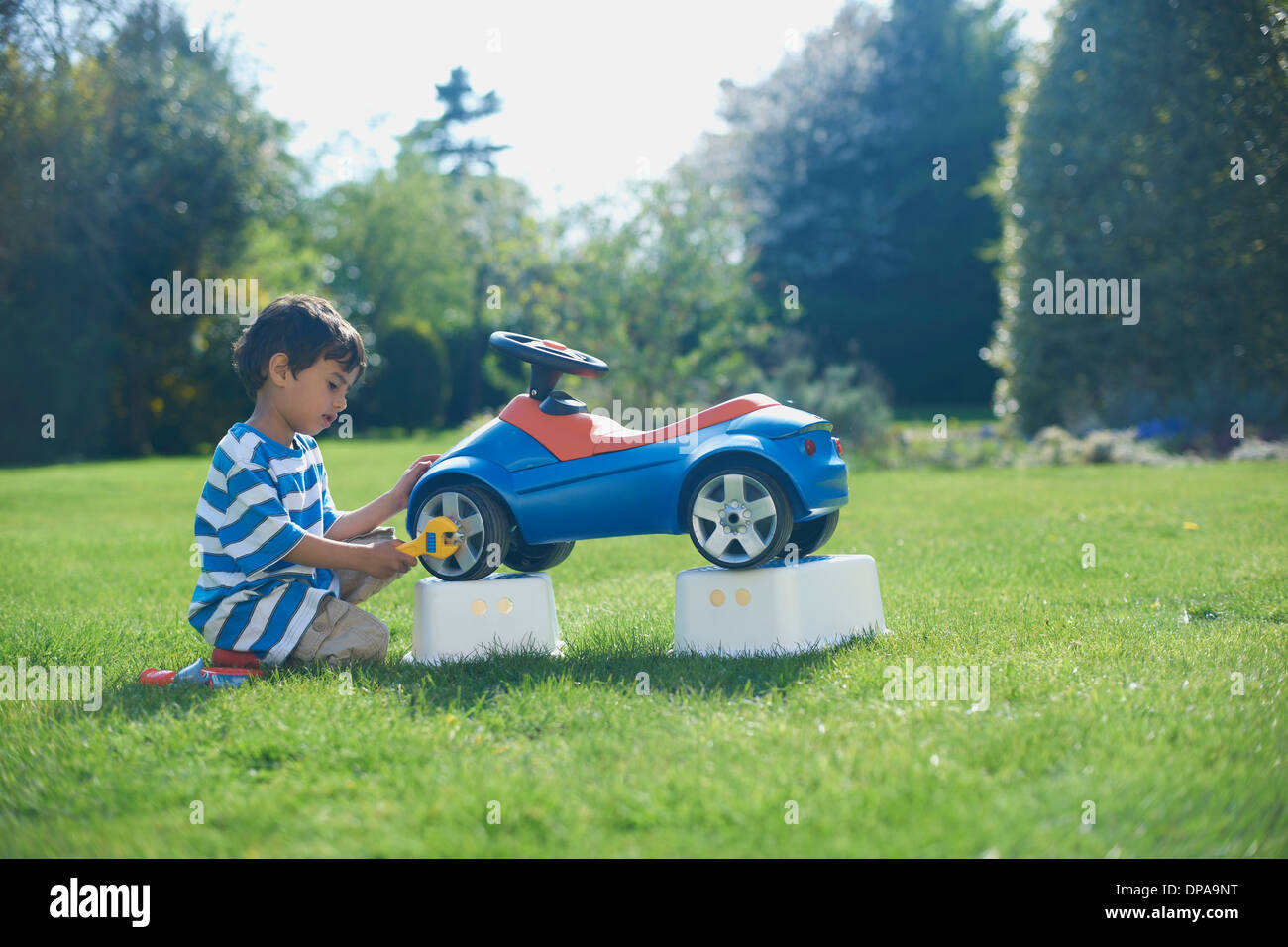 Boy pretending to fix toy car - Stock Image