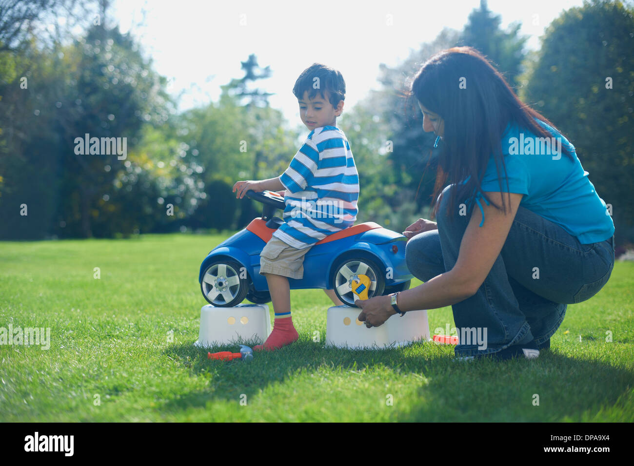 Mother and son pretending to fix toy car - Stock Image