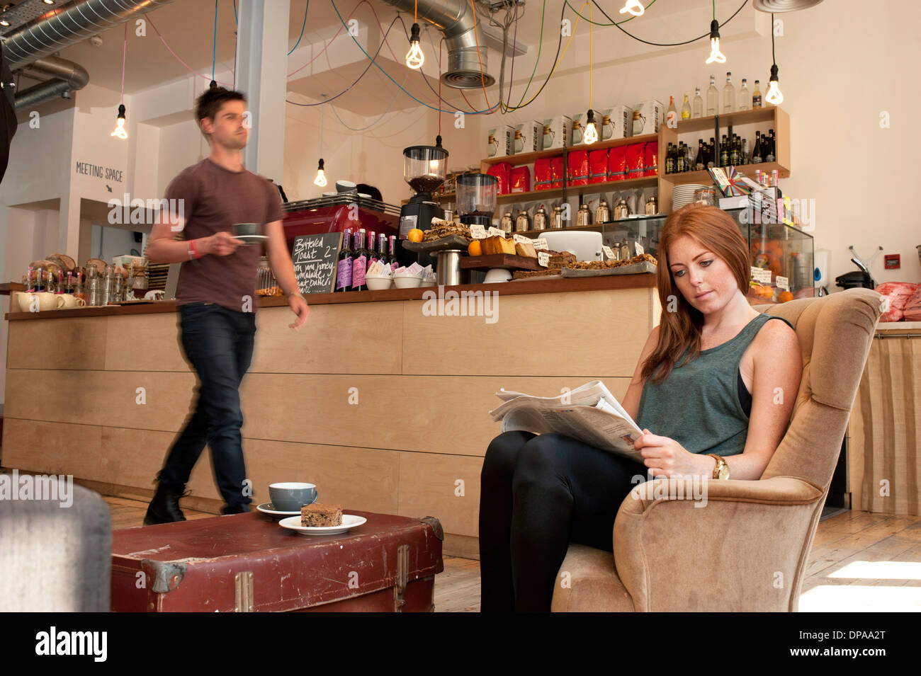 Young woman having tea and reading newspaper in cafe - Stock Image