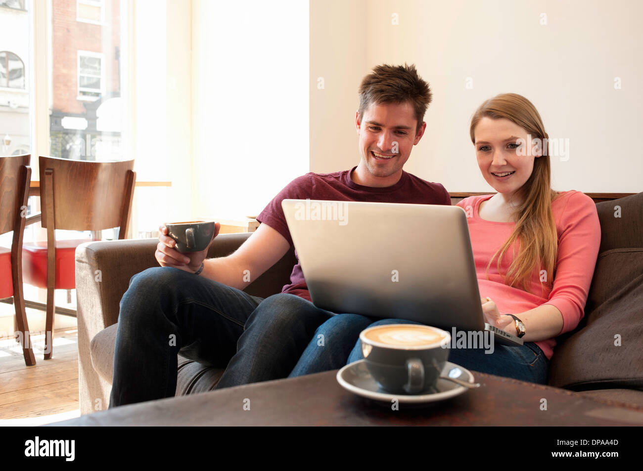 Young couple looking at personal computer in cafe - Stock Image
