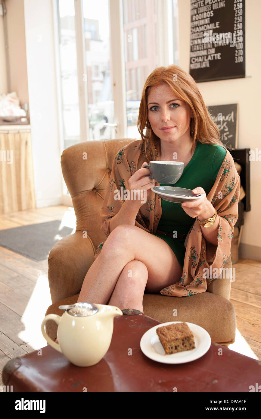 Portrait of young woman having tea and cake in cafe - Stock Image