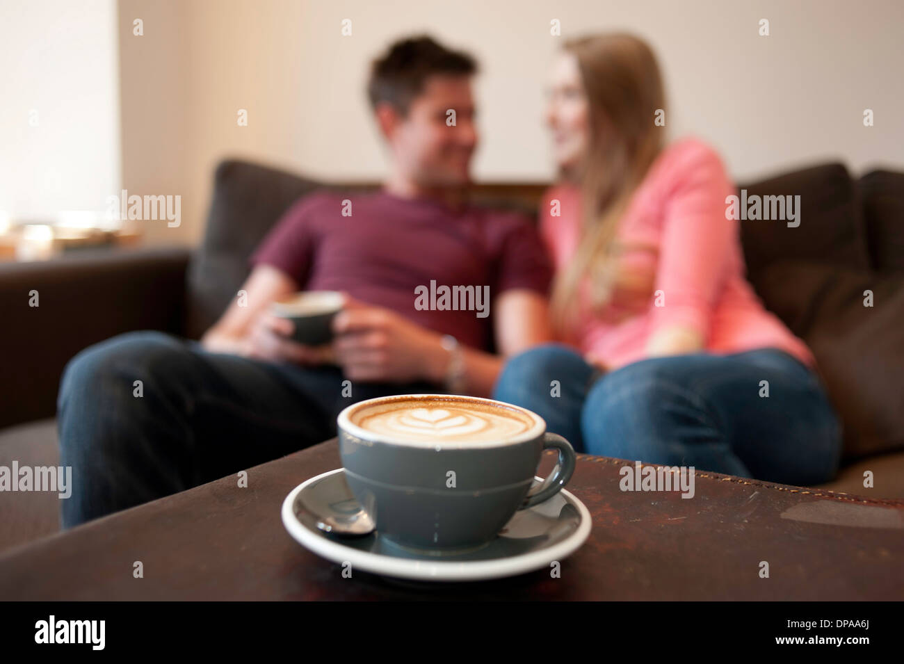 Young couple lounging on sofa in cafe - Stock Image