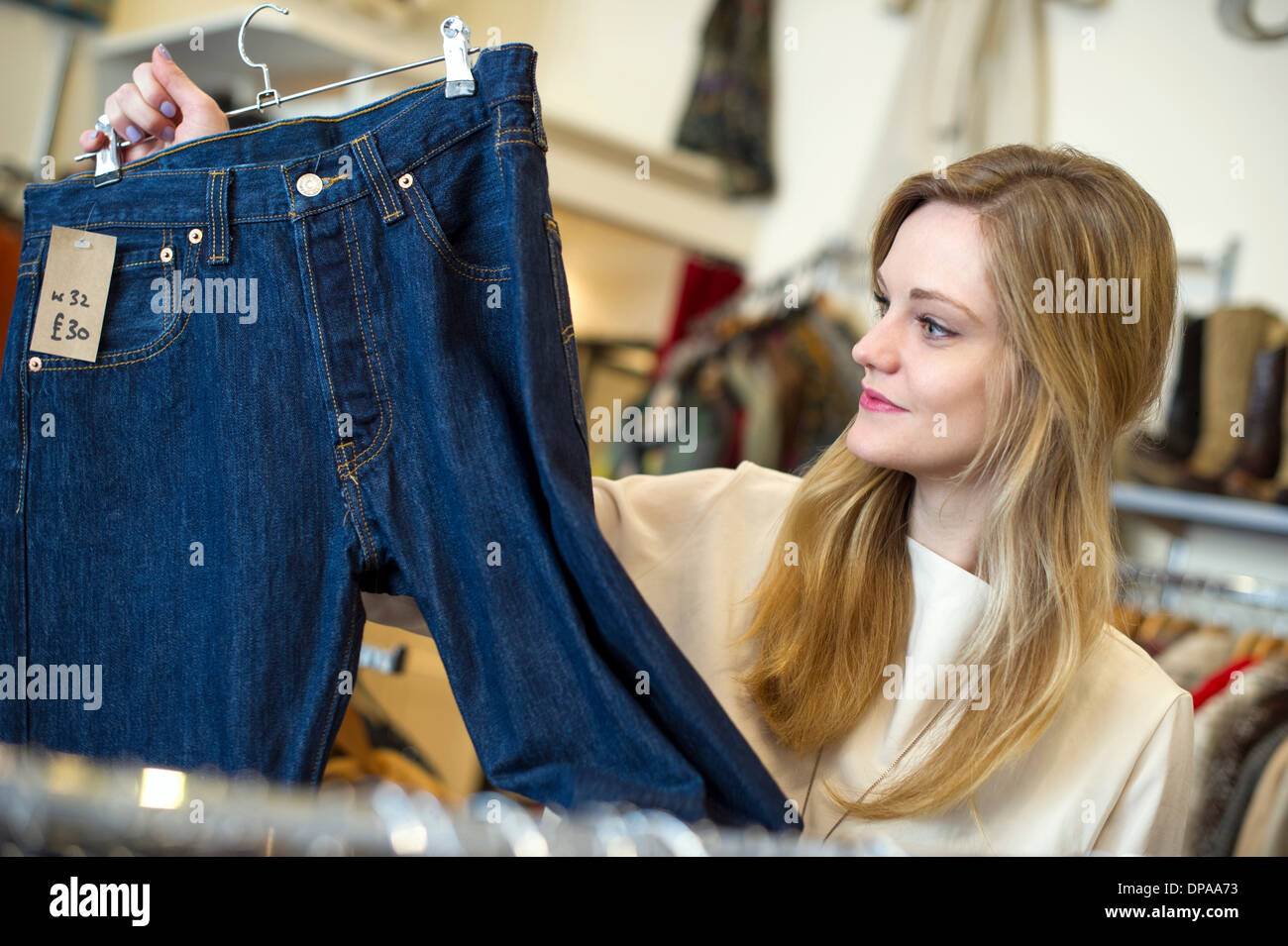 Woman looking at pair of jeans - Stock Image