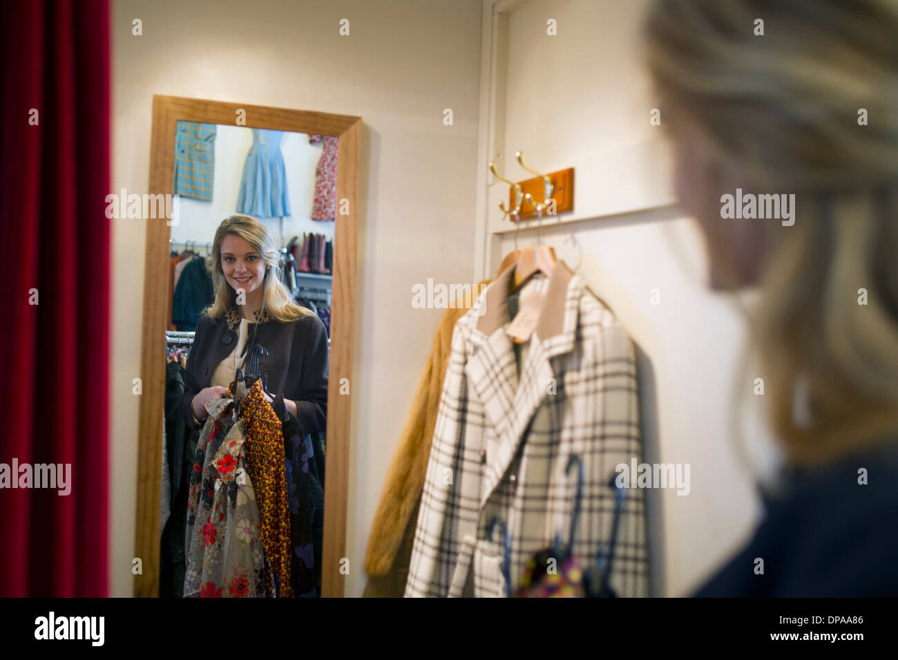 Woman taking clothes into fitting room - Stock Image