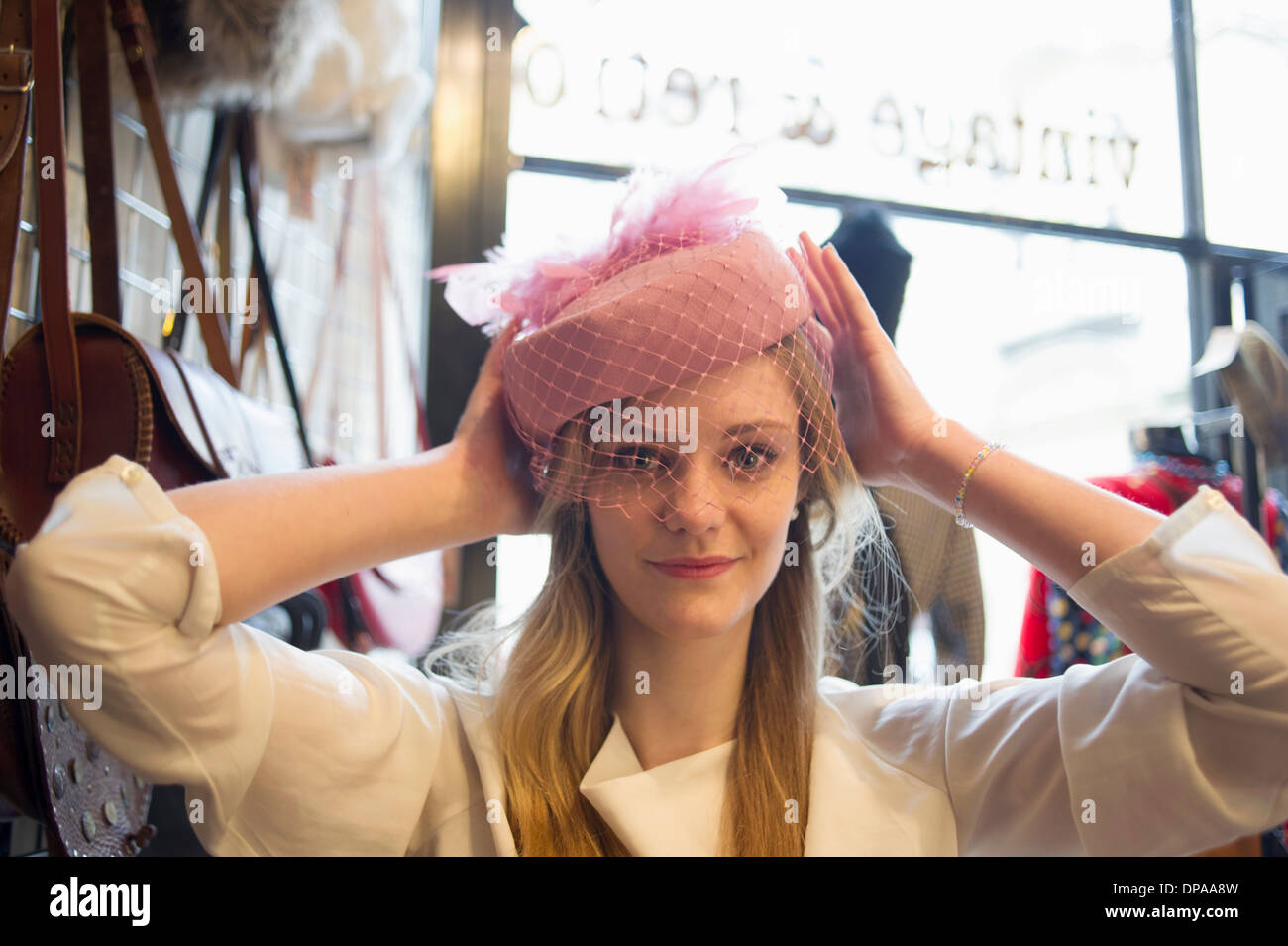 Woman trying on vintage hat - Stock Image
