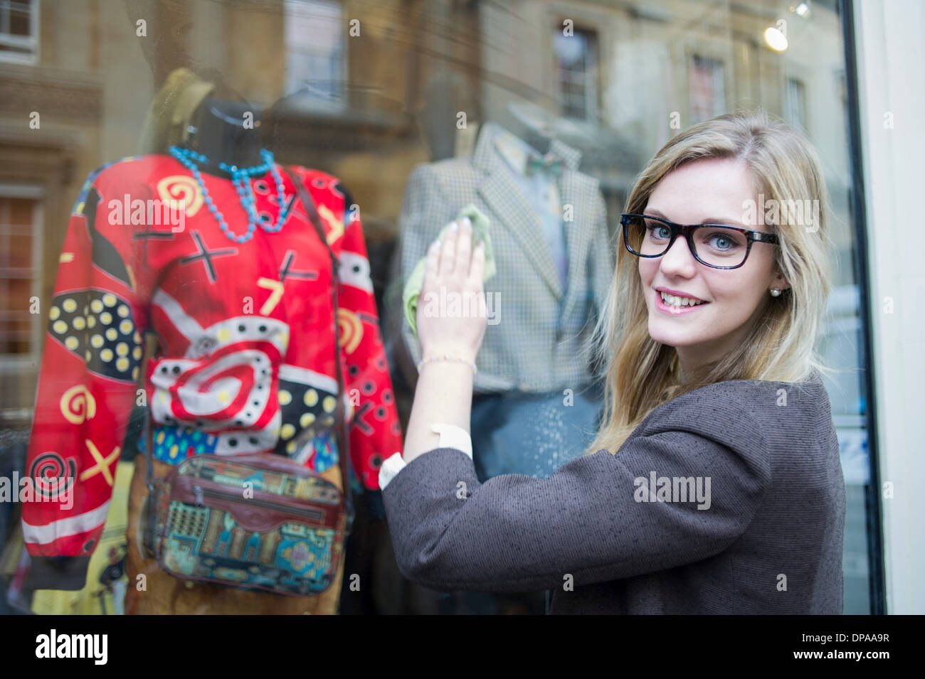 Woman cleaning window of clothes shop - Stock Image