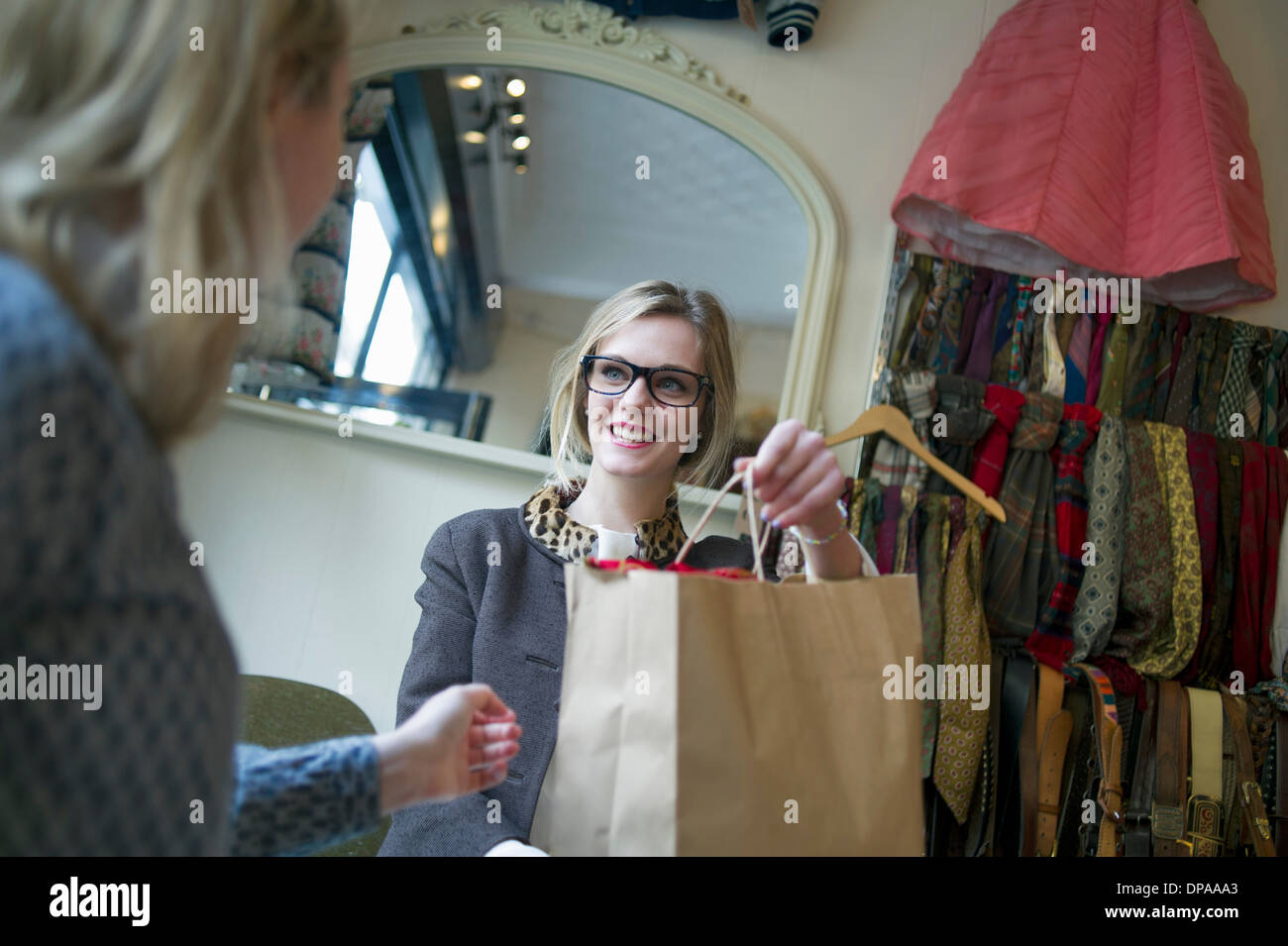Sales assistant handing shopping bag to lady - Stock Image