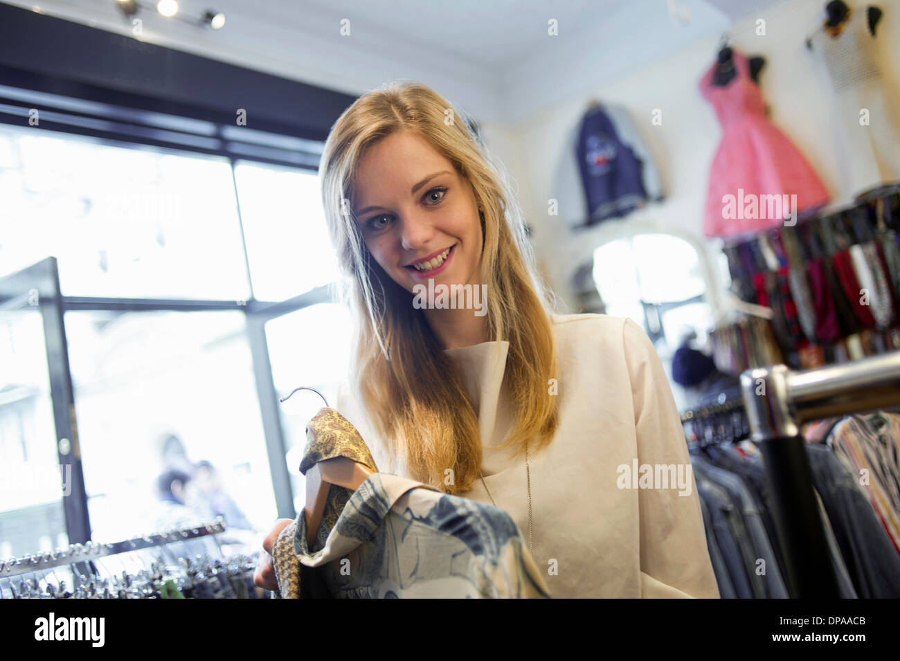 Woman holding top garment and scarf - Stock Image