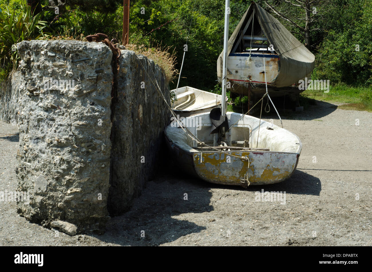 A small old boat sitting in the sand whne the tide is out in Newquay Stock Photo