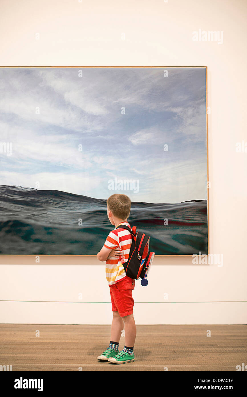 Young boy looking at picture in gallery - Stock Image