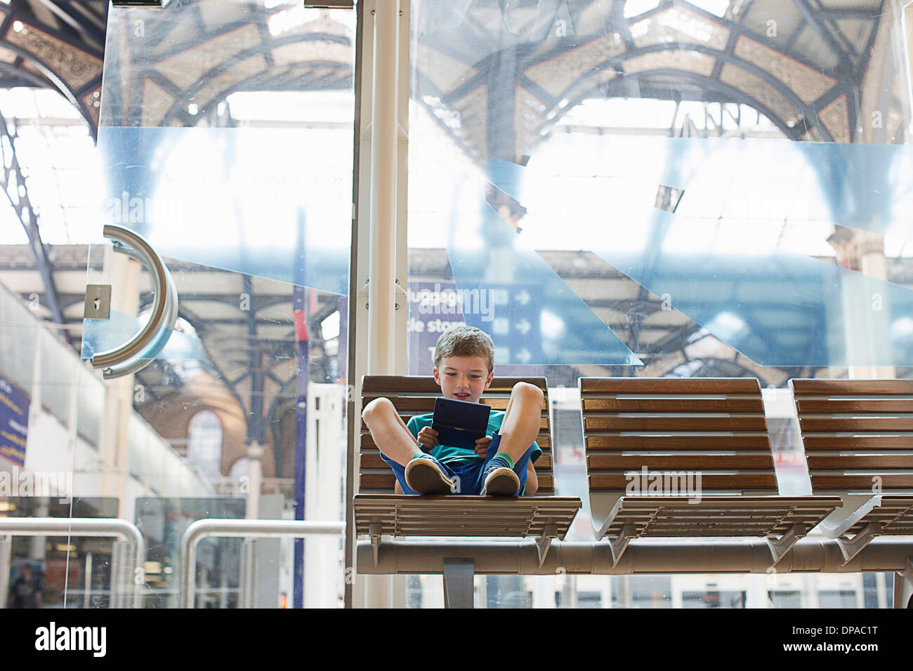 Young boy in train station waiting room playing handheld game - Stock Image