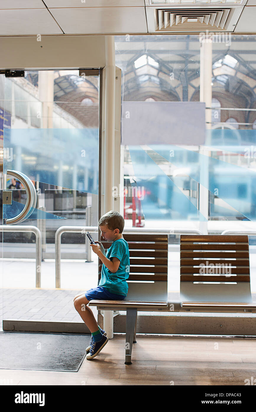 Young boy in train station waiting room playing electronic game - Stock Image