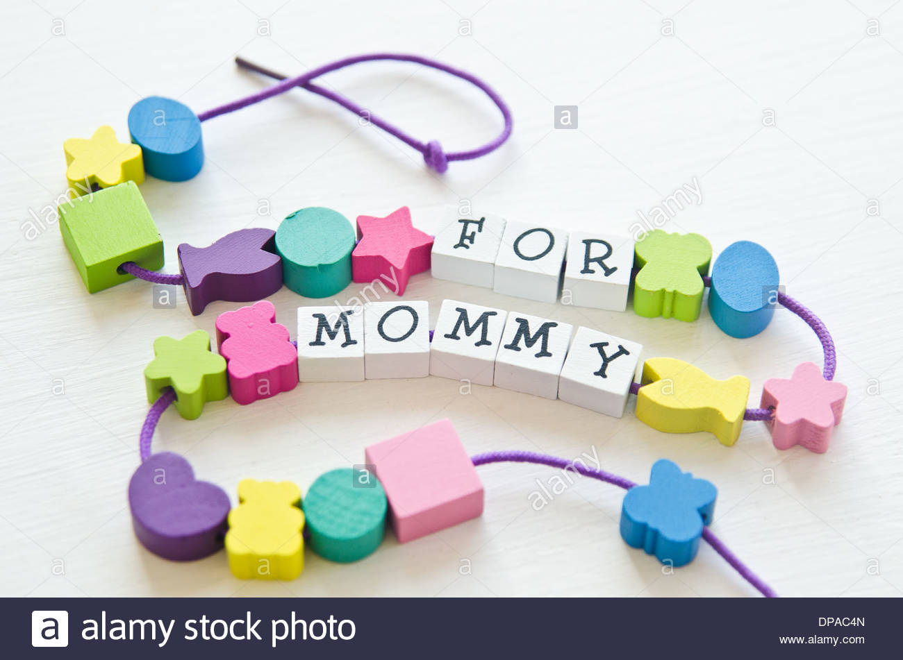 Colorful wooden toy beads in different shapes with letters that spell 'For mommy' strung together with cord on white background. - Stock Image