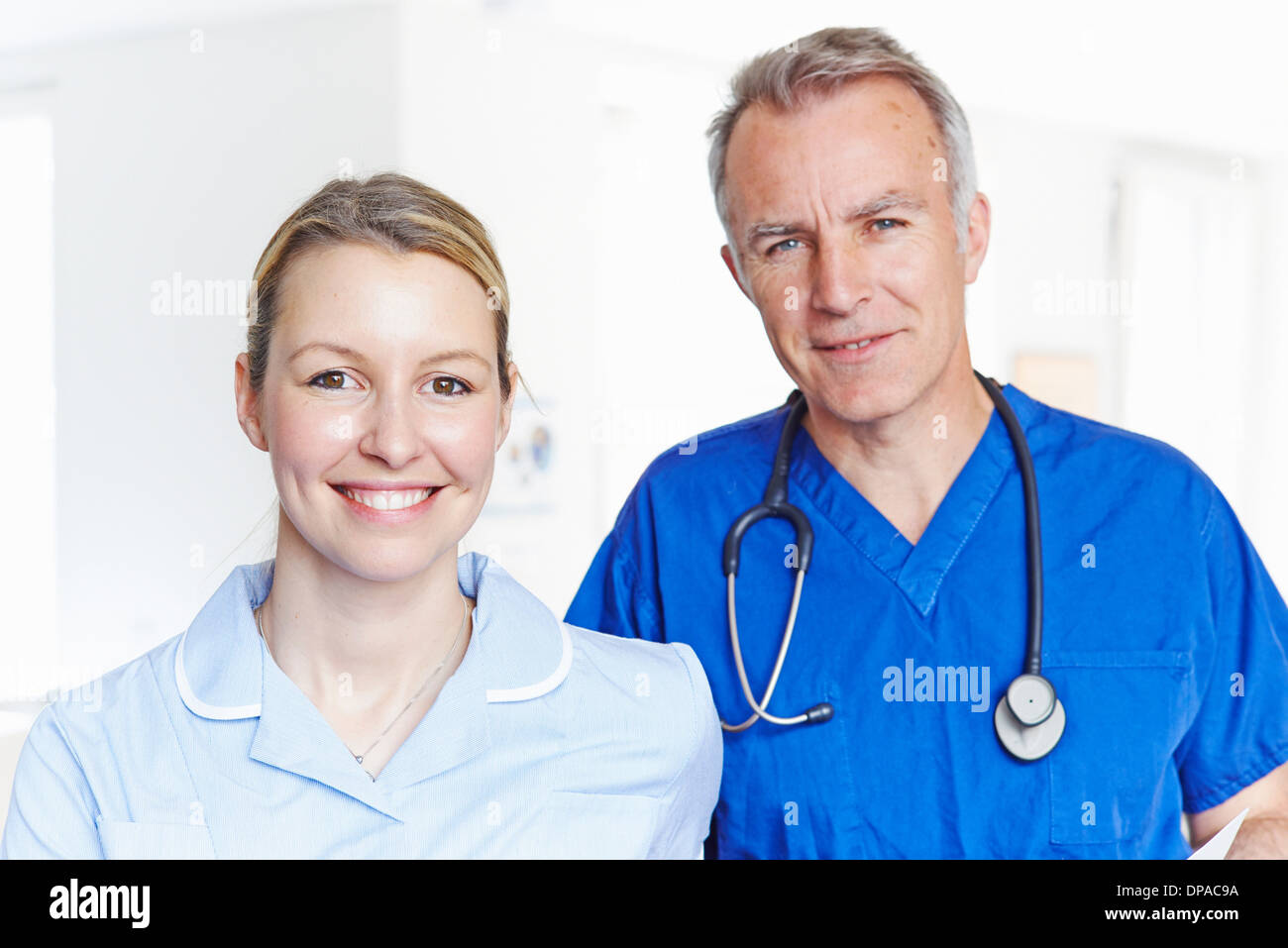 Portrait of doctor and nurse looking at camera - Stock Image