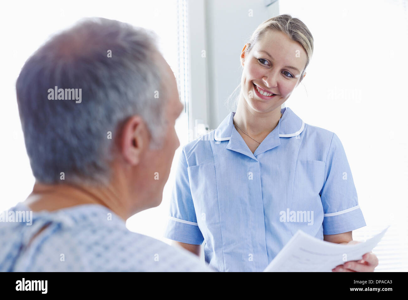 Nurse having conversation with patient - Stock Image
