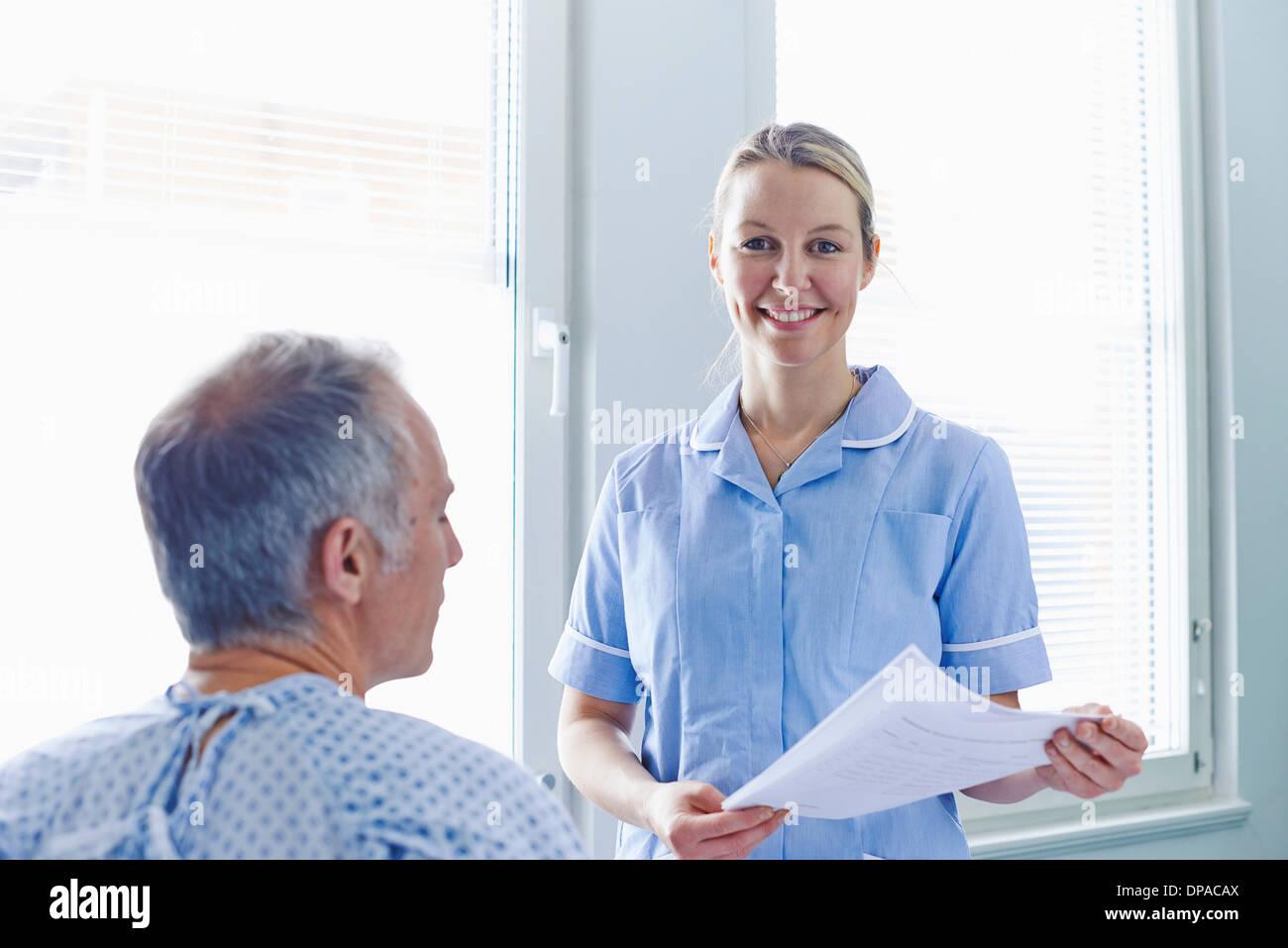 Nurse having conversation with patient - Stock Image