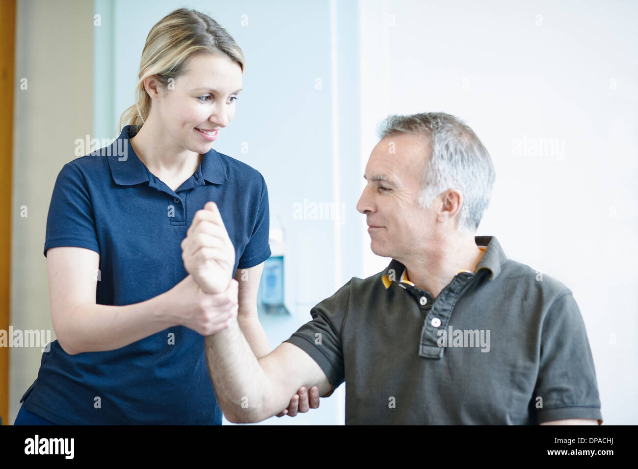 Physiotherapist helping man to do arm exercise - Stock Image