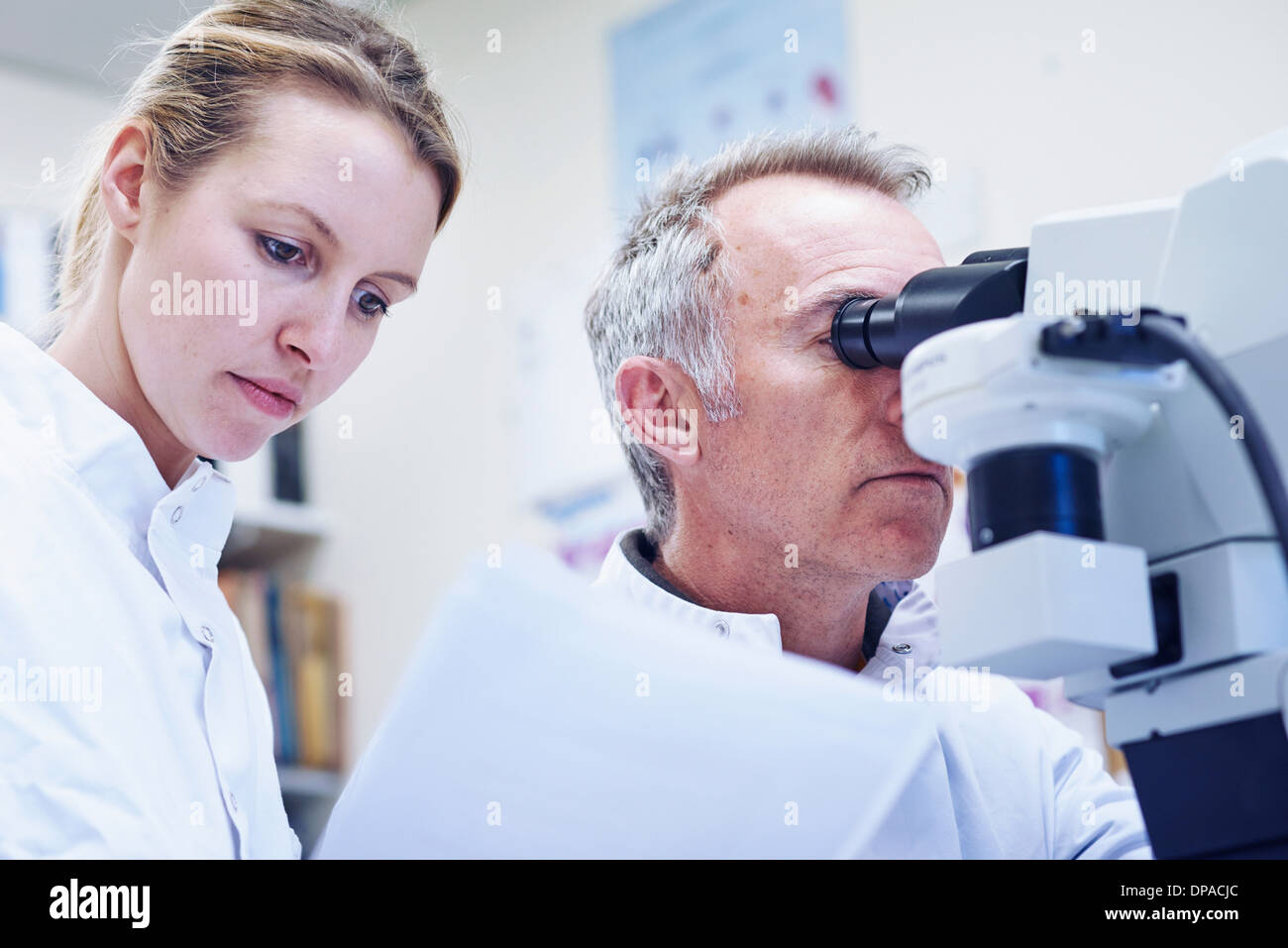 Man looking through microscope, woman looking at paperwork - Stock Image