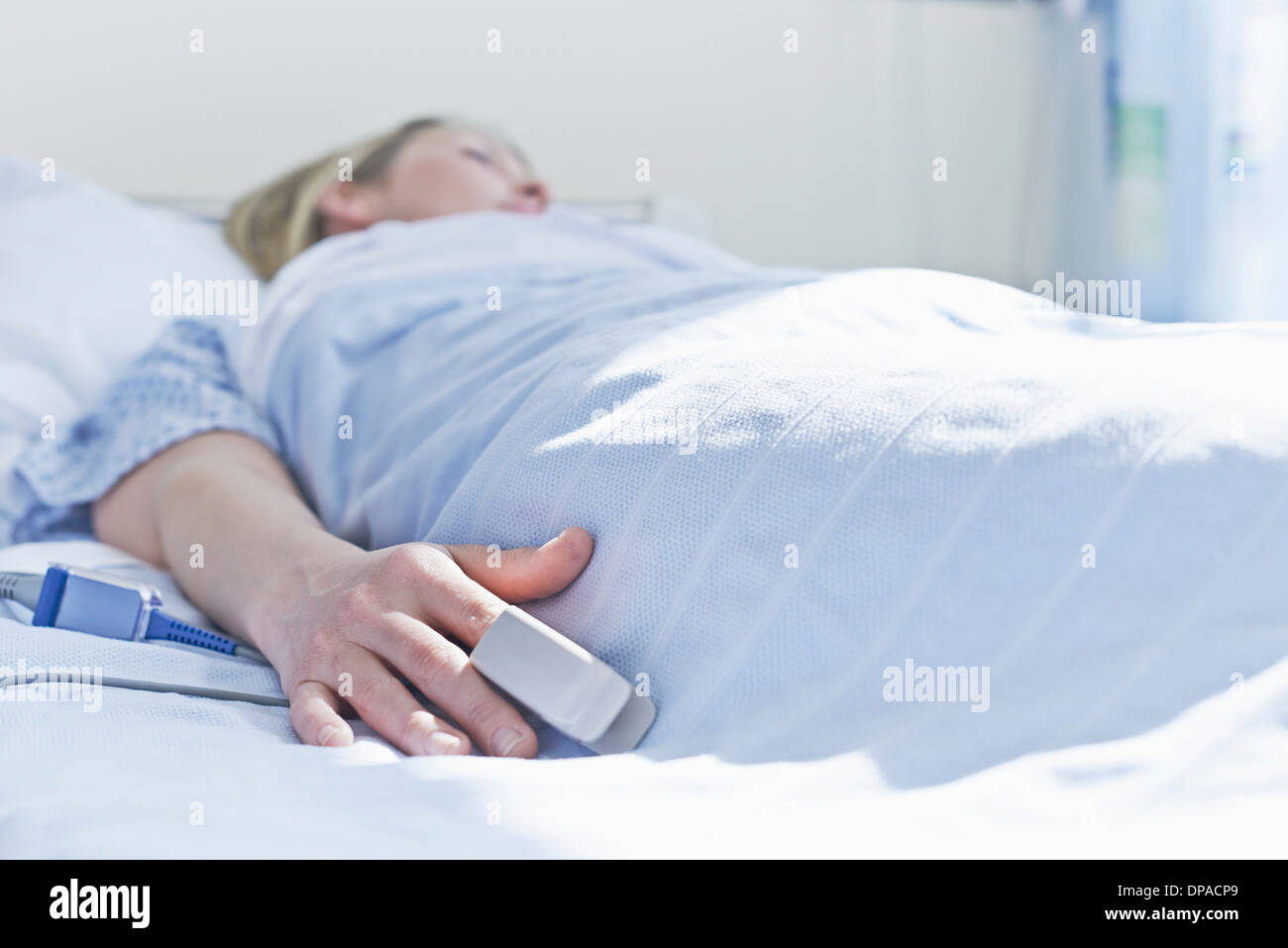 Patient lying on hospital bed with monitor on finger - Stock Image