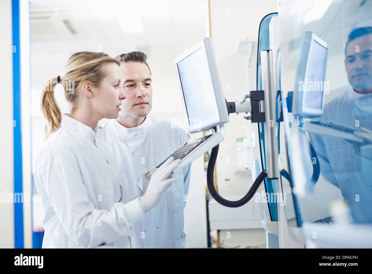 Researchers looking at computer in lab - Stock Image