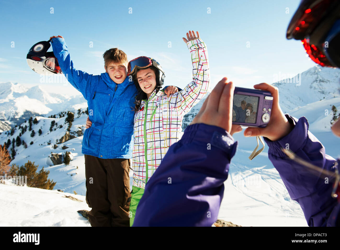 Girl photographing siblings, Les Arcs, Haute-Savoie, France - Stock Image