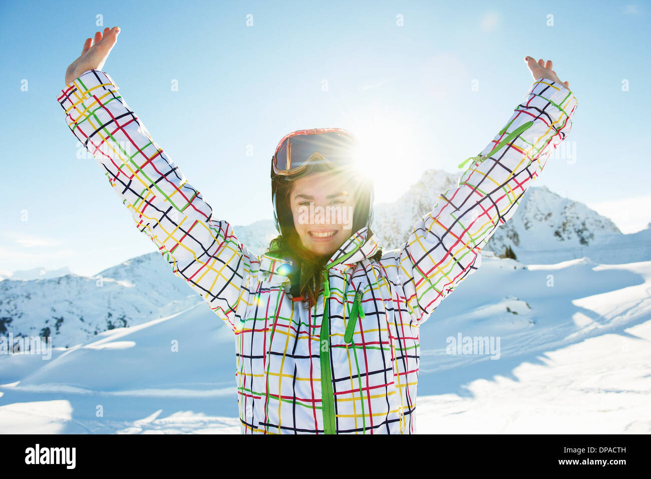 Portrait of teenage girl skier with arms outstretched, Les Arcs, Haute-Savoie, France - Stock Image