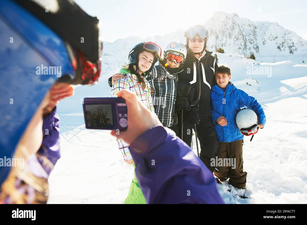 Girl photographing family, Les Arcs, Haute-Savoie, France - Stock Image