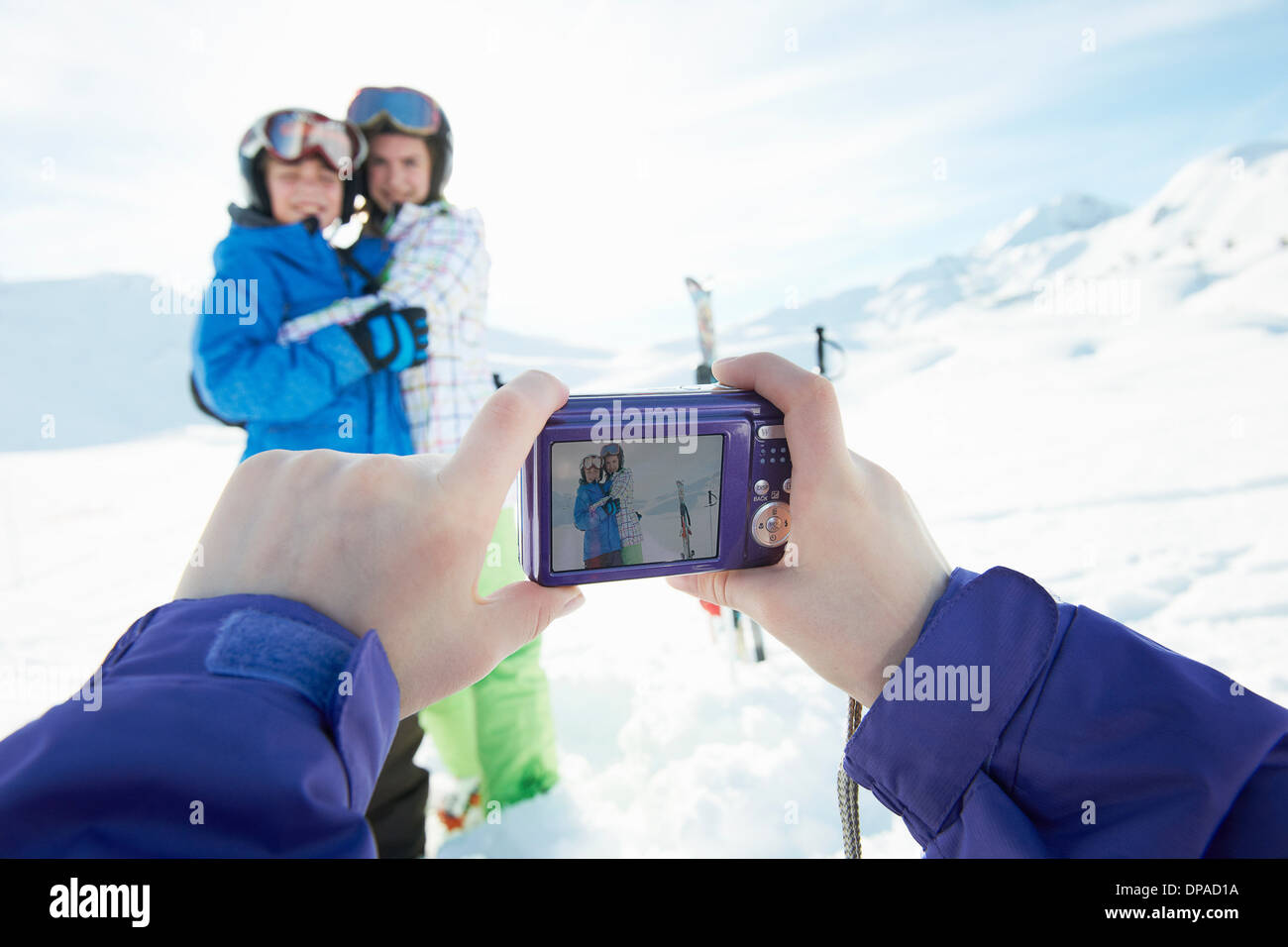 Sister photographing siblings in snow, Les Arcs, Haute-Savoie, France Stock Photo