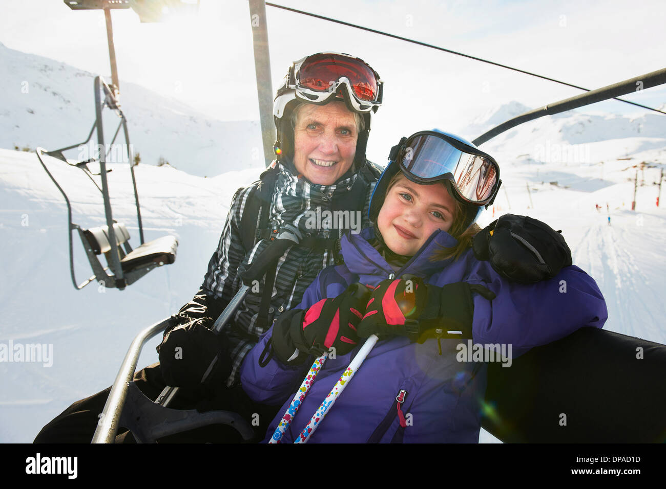 Portrait of grandmother and granddaughter on ski lift, Les Arcs, Haute-Savoie, France - Stock Image