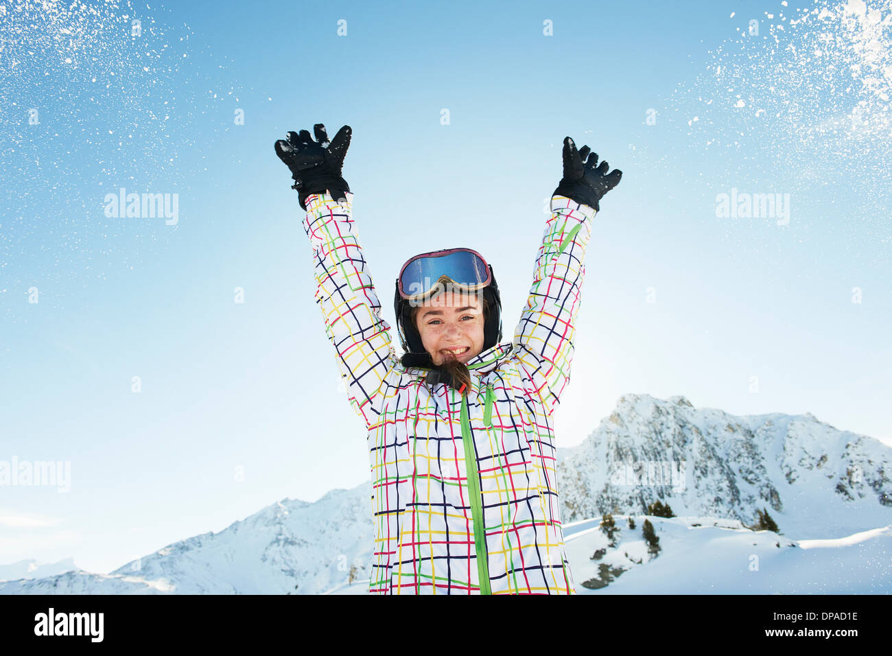 Portrait of teenage girl skier with arms raised, Les Arcs, Haute-Savoie, France - Stock Image