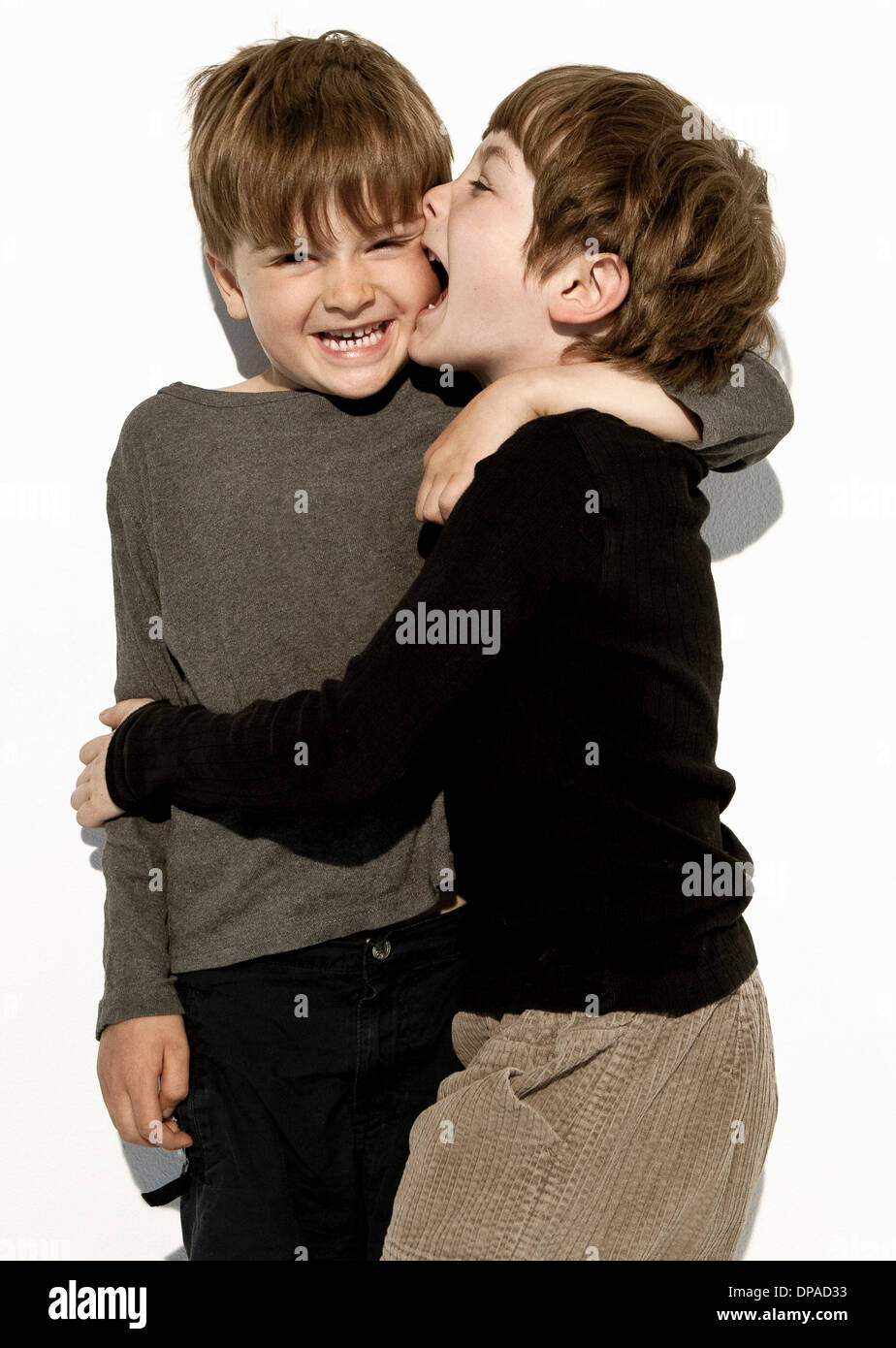 Boy biting brother's cheek - Stock Image