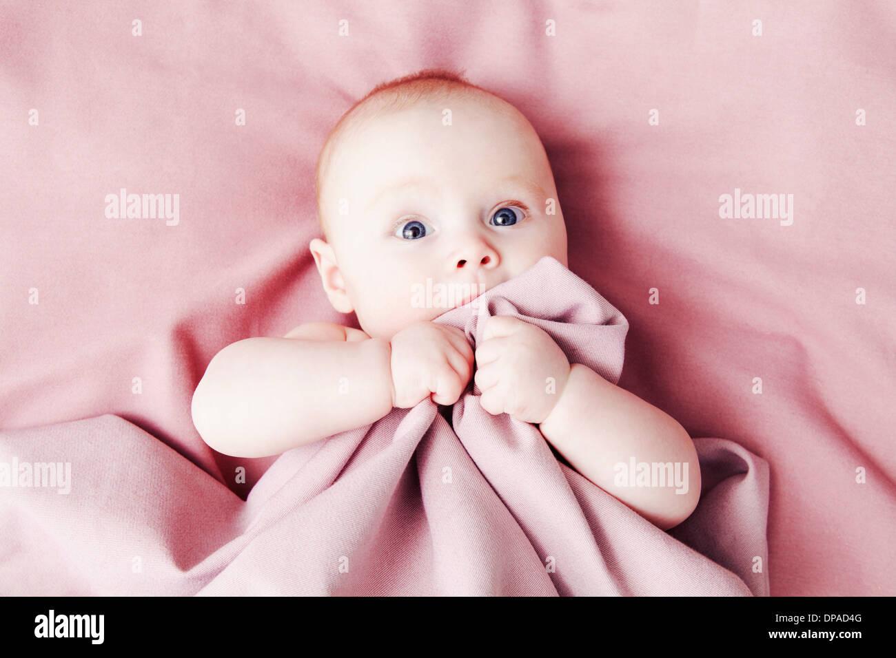 Baby girl on pink blanket - Stock Image