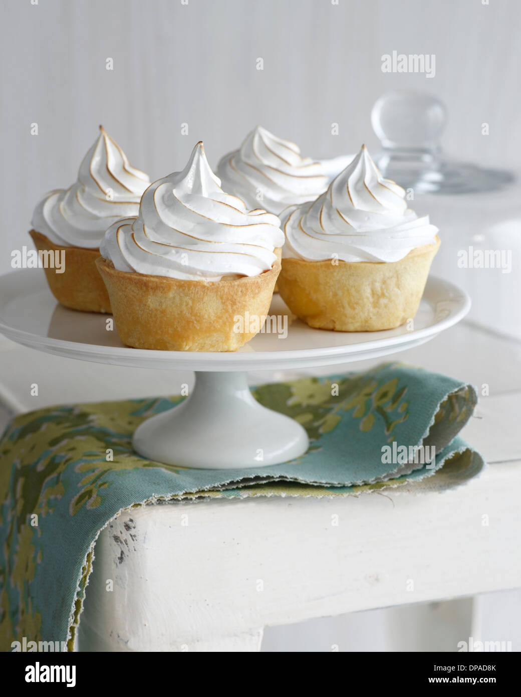Banana meringue tarts on cake stand - Stock Image