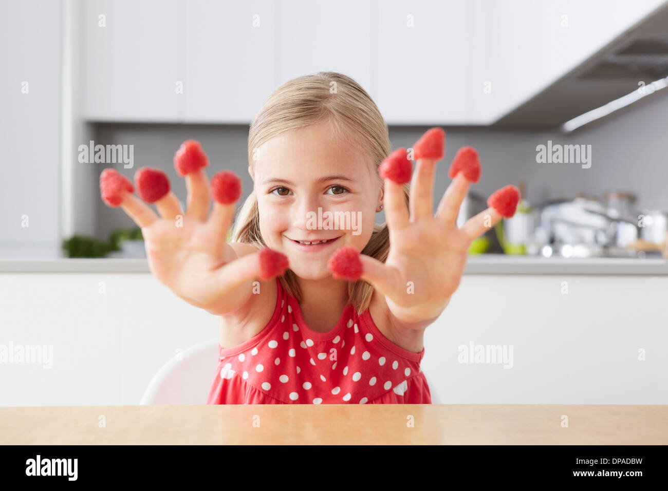 Girl putting raspberries on fingers - Stock Image