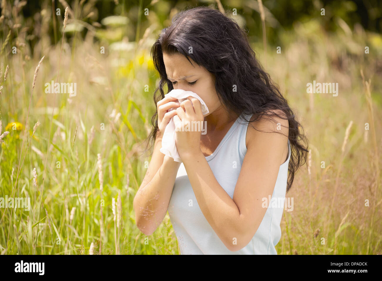 Girl wiping nose with tissue - Stock Image