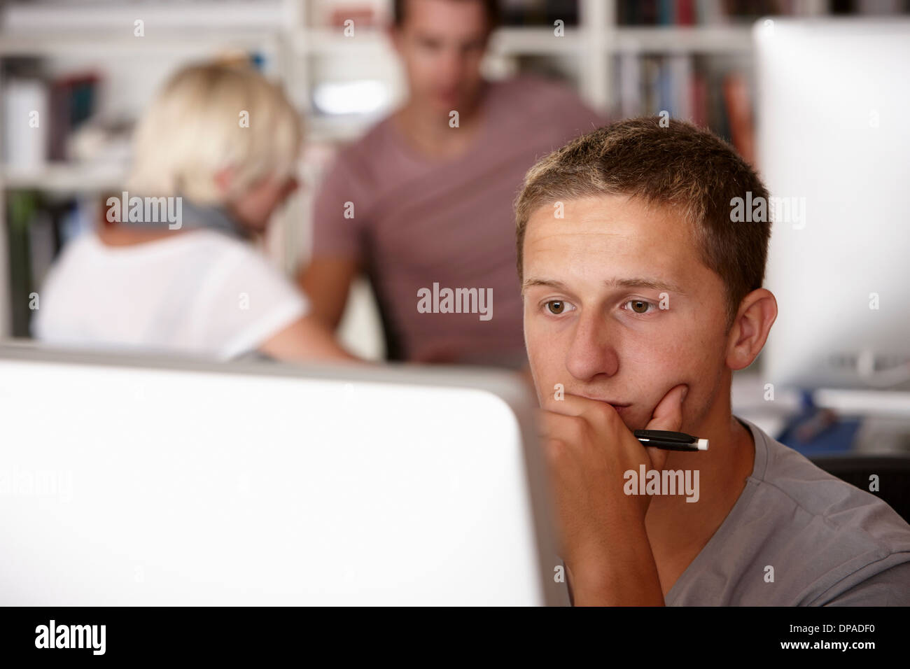 Young man using computer, hand on chin Stock Photo