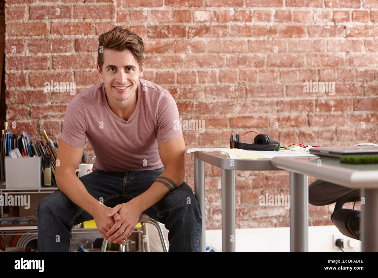 Portrait of young man sitting on chair in creative office - Stock Image
