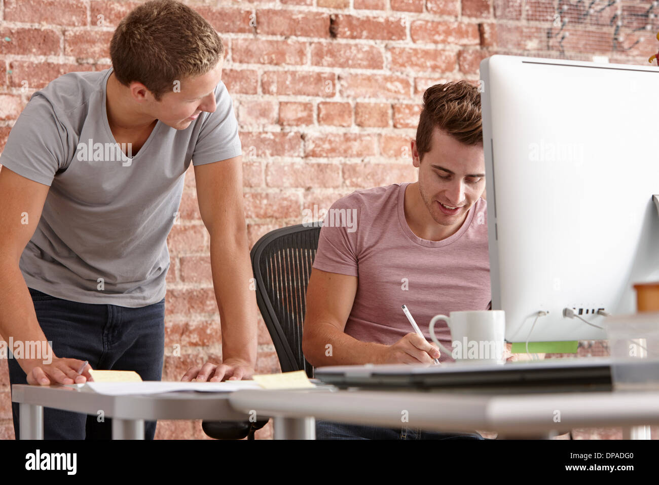 Young men talking at desk with computer - Stock Image