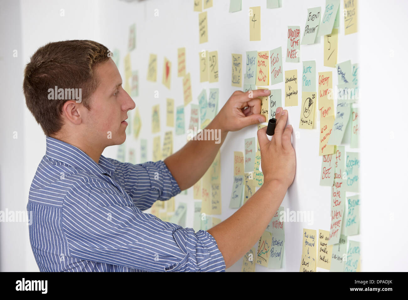 Young man sticking adhesive note on wall - Stock Image