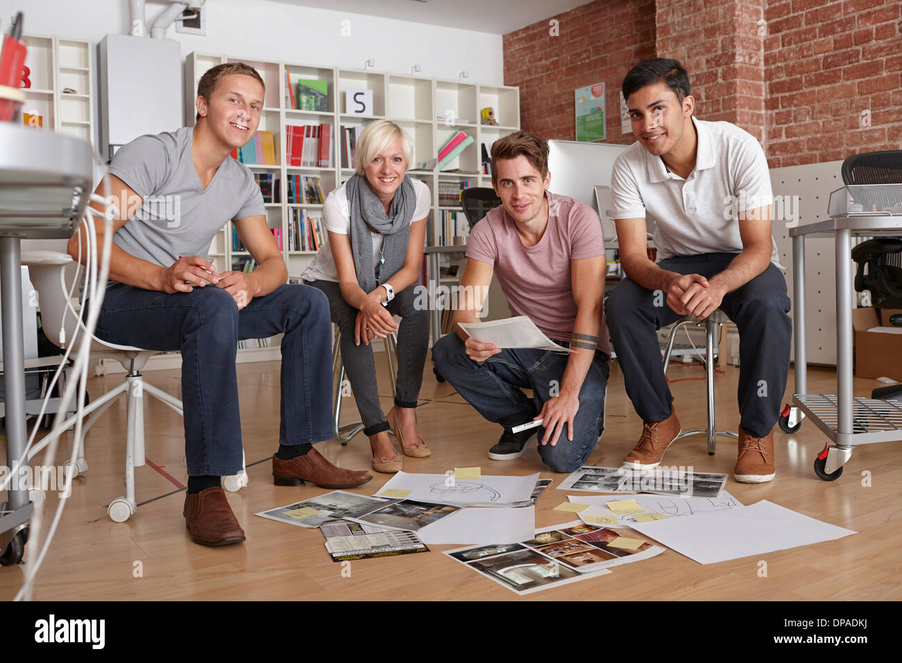 Portrait of colleagues with papers on floor - Stock Image