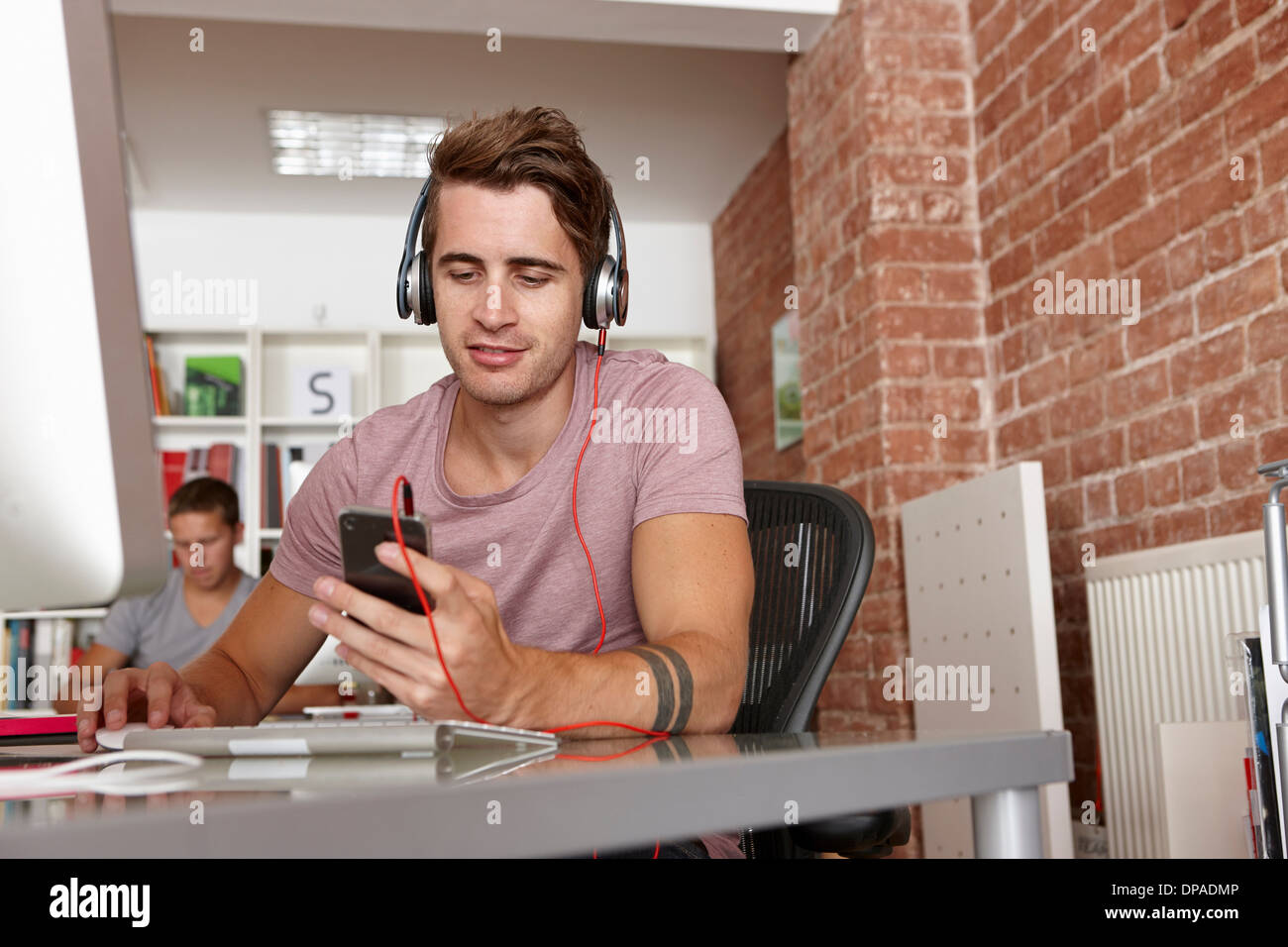 Young man wearing headphones using mp3 player - Stock Image