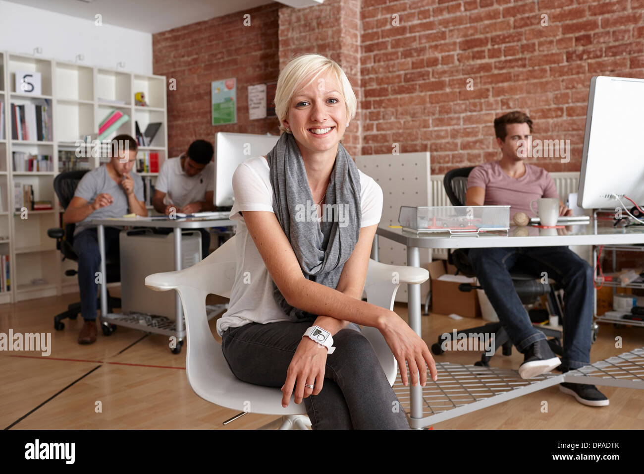 Portrait of mid adult woman sitting on chair in creative office - Stock Image