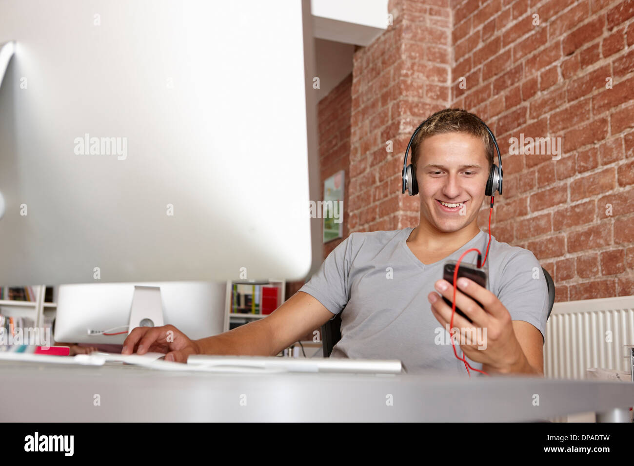 Young man at work using mp3 player - Stock Image